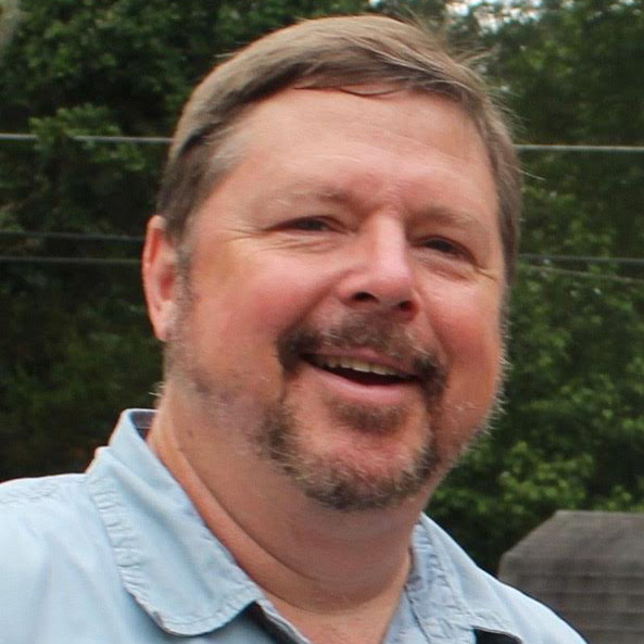 A white-presenting male with light brown hair and a light beard, smiling, wearing a light blue button-down shirt.
