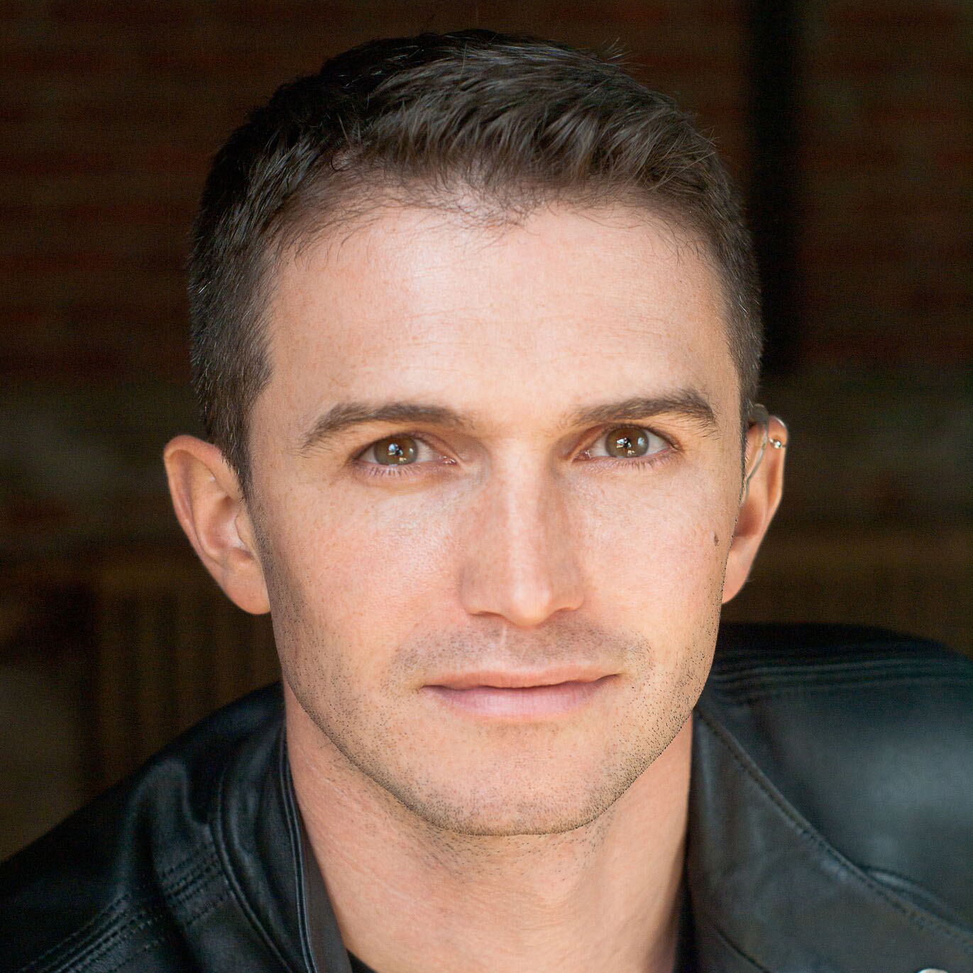 A white-presenting male with short brown hair, a soft smile and sharp green/brown eyes, wearing a leather jacket.